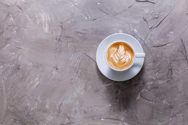 Latte art in tazza di cappuccino. vista dall'alto su sfondo grigio cemento