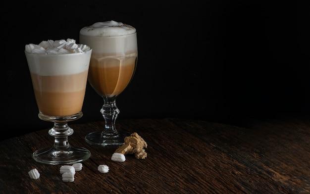 Caffè latte con schiuma gustosa in vetro con marshmallow sul tavolo rustico scuro su sfondo nero