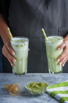 Latte a base di tè verde matcha e latte di soia da vicino. il barista della donna tiene in sue mani due vetri con una bevanda vegetariana.