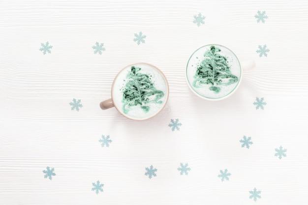 Latte caffè invernale con arte dell'albero di capodanno in tazza sul tavolo bianco