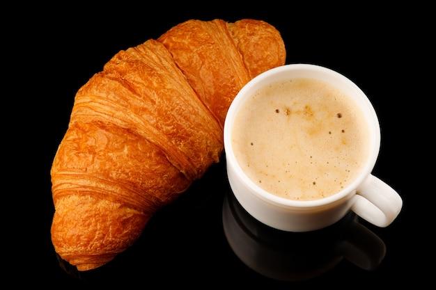 Latte con schiuma in una tazza e croissant