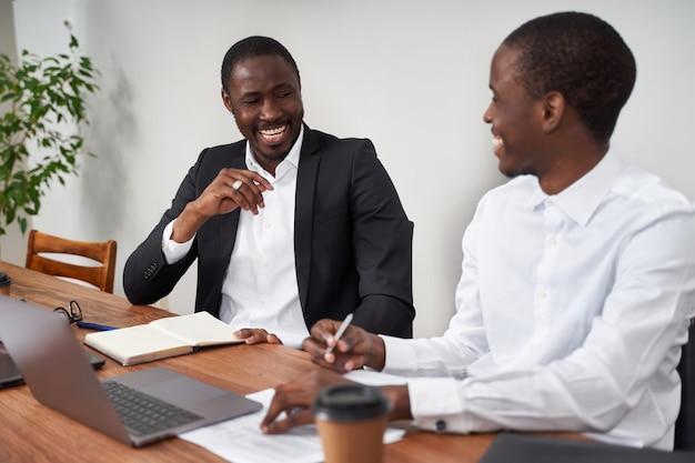 Uomini d'affari afroamericani di risata che discutono del lavoro di ufficio con un collega ad una tavola in un ufficio