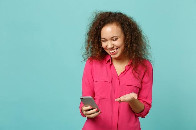 Ridere ragazza africana in abiti casual rosa utilizzando il telefono cellulare digitando messaggio sms isolato su sfondo blu muro turchese in studio. persone sincere emozioni, concetto di stile di vita. mock up copia spazio.