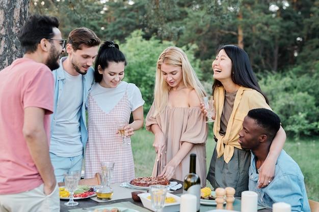 Ragazza asiatica di risata con bicchiere di vino che abbraccia il giovane africano durante il raduno di amici sotto l'albero per la cena in ambiente naturale