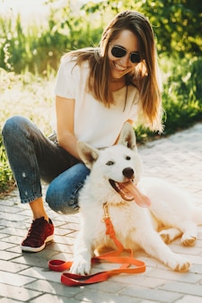 Ridere bella giovane donna in abiti estivi e occhiali da sole seduto su hunkers con il suo cane bianco felice