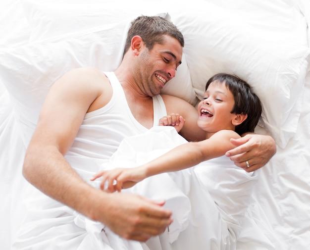 Ragazzo che ride con suo padre sdraiato su un letto a casa