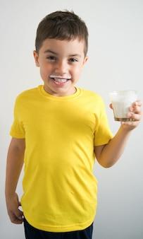 Ragazzo che ride in maglietta gialla con i baffi di kefir o latte e bicchiere in mano