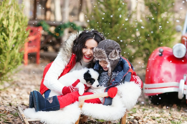 Mamma bruna di risata e suo figlio seduti in slitta con cucciolo husky davanti all'auto di babbo natale