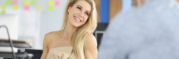 La donna d'affari ridente comunica con il partner commerciale sul posto di lavoro