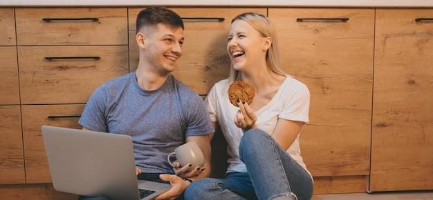 Ridendo coppia caucasica mangiando biscotti e utilizzando un computer portatile in cucina sul pavimento insieme