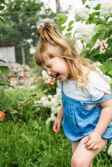 Ridendo allegra bambina nel villaggio, con gli stivali di gomma.