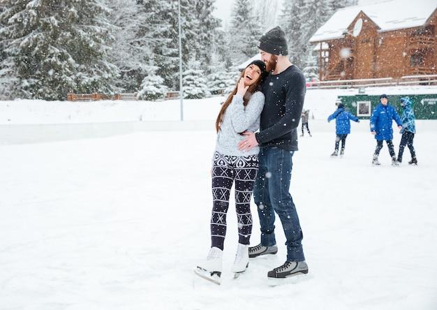 Ridere coppia in pattini da ghiaccio parlando all'aperto con la neve sullo sfondo
