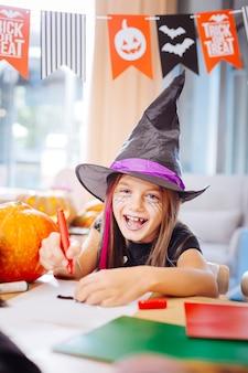 Ridere e disegnare. ragazza dagli occhi azzurri che indossa il costume di halloween del mago che ride mentre disegna immagini spaventose