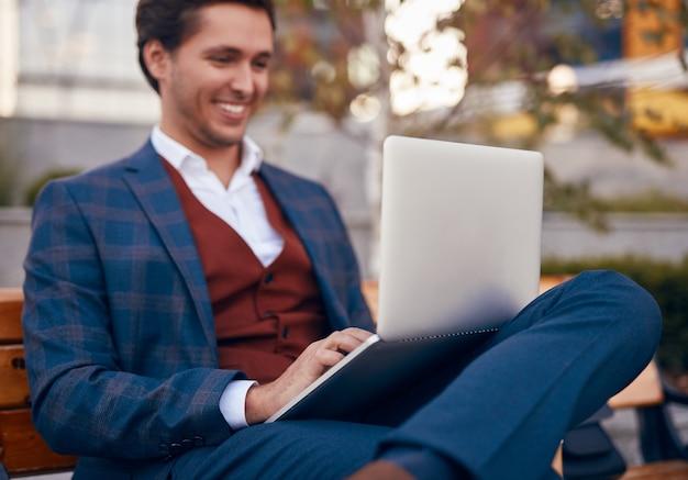 Imprenditore di risata che lavora al computer portatile sulla panchina della città