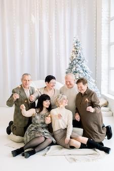 Ridendo famiglia di tre generazioni con stelle filanti nel periodo natalizio