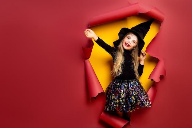 Ridendo divertente ragazza bambino in un costume da strega di halloween alla ricerca, sorridente e spaventa attraverso un buco di sfondo di carta rossa, gialla.
