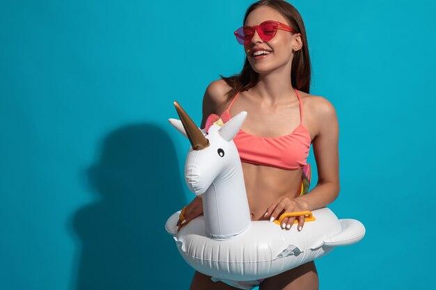 Ragazza che ride in costume da bagno e occhiali da sole con anello da bagno unicorno sulla parete blu