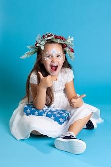 Ridere le ragazze in un abito bianco, con indosso una ghirlanda e scarpe da ginnastica seduto sul pavimento tenendo il regalo