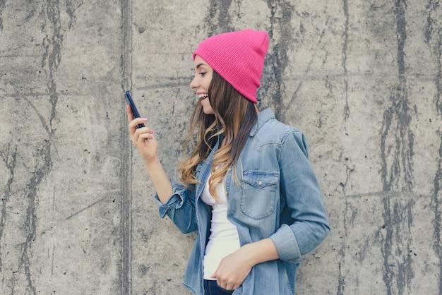 Ridendo felice ragazza eccitata in jeans abbigliamento e cappello rosa utilizzando smartphone e fotocamera frontale per la comunicazione attraverso internet sulla strada