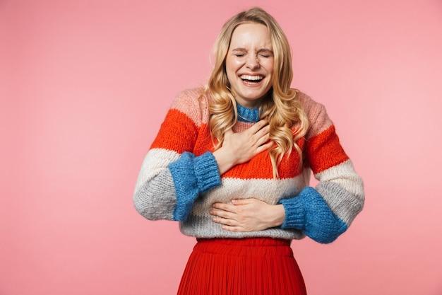 Una risata felice eccitata giovane bella donna in posa isolata su un muro rosa