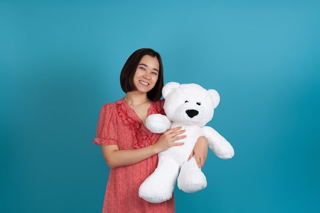 Ridendo gioiosa donna in un abito rosso in possesso di un orsacchiotto bianco da un lato