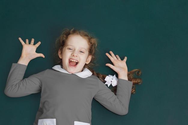Bambina ridendo in piedi vicino alla lavagna. ritorno a scuola e concetto di facile apprendimento. Foto Premium