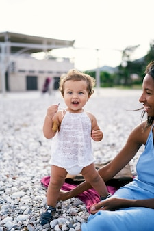 La bambina ridente con un giocattolo in mano sta accanto a sua madre seduta sulla spiaggia