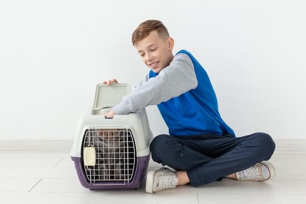 Ridendo ragazzino positivo tiene una gabbia con un gatto scottish fold accanto a lui seduto sul pavimento in un nuovo appartamento. concetto di protezione degli animali domestici. copyspace