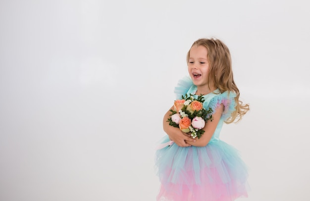 La piccola principessa ridente tiene un mazzo di fiori freschi su uno sfondo bianco con una copia dello spazio