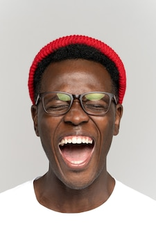 Ridendo positivo giovane hipster uomo in bicchieri e cappello rosso di buon umore con gli occhi chiusi