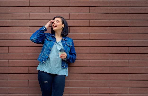 Ridere piuttosto brunnete ragazza caucasica in una giacca di jeans blu in piedi davanti al muro di mattoni tenendo in mano il caffè caldo.