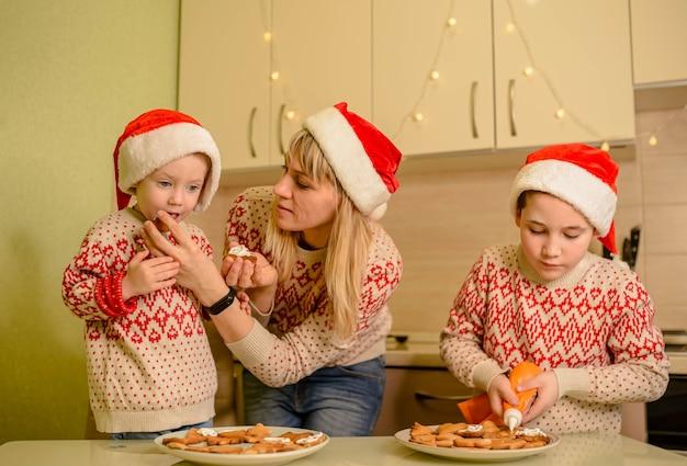 Figli che ridono e mamma carina che decora i biscotti di natale di pan di zenzero al forno