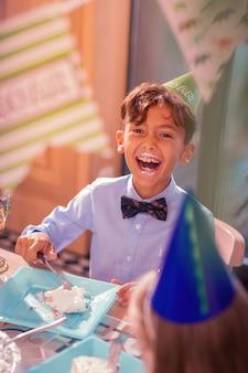 Ridere mentre si mangia. ragazzo di compleanno emotivo che indossa il cappello del partito e che ride con la bocca aperta mentre mangia la torta