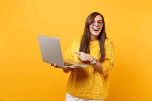 Donna che ride in maglione di pelliccia, occhiali da vista a cuore che lavorano puntando il dito indice sul computer pc portatile isolato su sfondo giallo brillante. persone sincere emozioni, concetto di stile di vita. zona pubblicità.