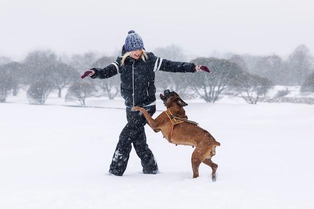 La donna che ride gioca con il cane boxer a winter park. amore e amicizia.