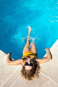 Donna che ride in piscina. sta prendendo il sole in una piscina. indossa costume da bagno e cappello gialli.