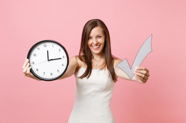 Ridere donna in abito bianco che mostra segno di spunta e sveglia rotonda