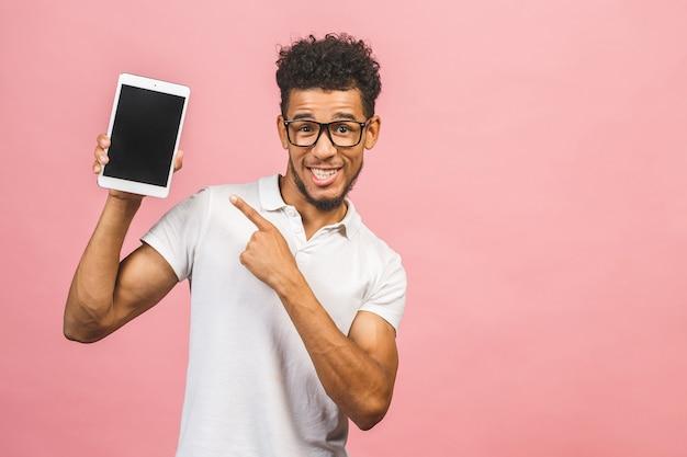 Ridendo giovane maschio afroamericano che tiene un tablet touch pad