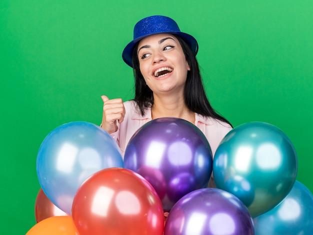 Ridendo giovane bella donna che indossa il cappello da festa in piedi dietro i palloncini che mostra il pollice in alto isolato sul muro verde