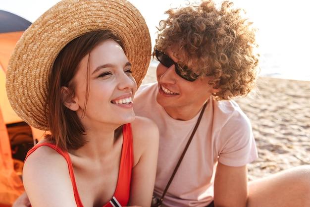 Ridendo coppia giovane seduti insieme in spiaggia, in campeggio