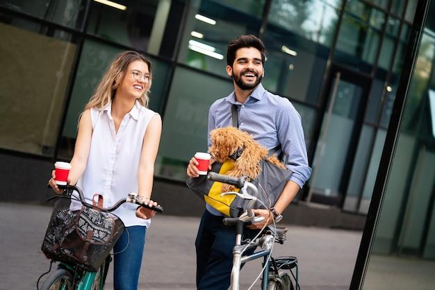 Ridendo giovane coppia con cane di piccola taglia a piedi, parlando in città