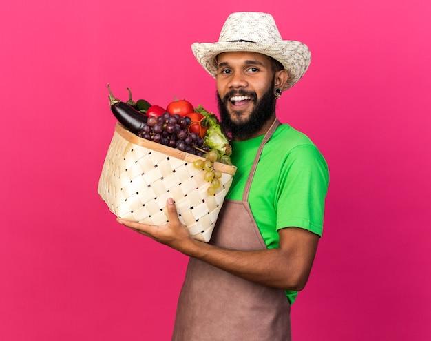 Ridendo giovane giardiniere afro-americano che indossa cappello da giardinaggio con cesto di verdure
