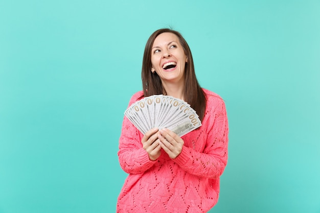 Ridere giovane ragazza in maglia maglione rosa cercando tenere in mano un sacco di dollari banconote denaro contante isolato su priorità bassa blu della parete in studio. concetto di stile di vita della gente. mock up copia spazio.