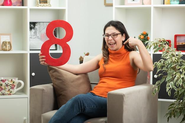 Ridendo giovane bella donna con gli occhiali tenendo la figura rossa otto e indicando se stessa seduta sulla poltrona in soggiorno a marzo giornata internazionale della donna