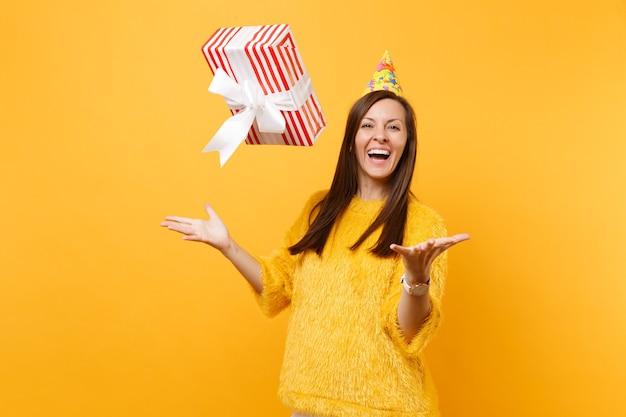 Ridere giovane donna in festa di compleanno cappello vomitare scatola rossa con regalo presente, celebrare e godersi la vacanza isolato su sfondo giallo brillante. persone sincere emozioni, concetto di stile di vita.