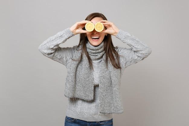 Ridere giovane donna in maglione grigio, sciarpa che copre gli occhi con limoni isolati su sfondo grigio muro. stile di vita sano, persone sincere emozioni, concetto di stagione fredda. mock up copia spazio.