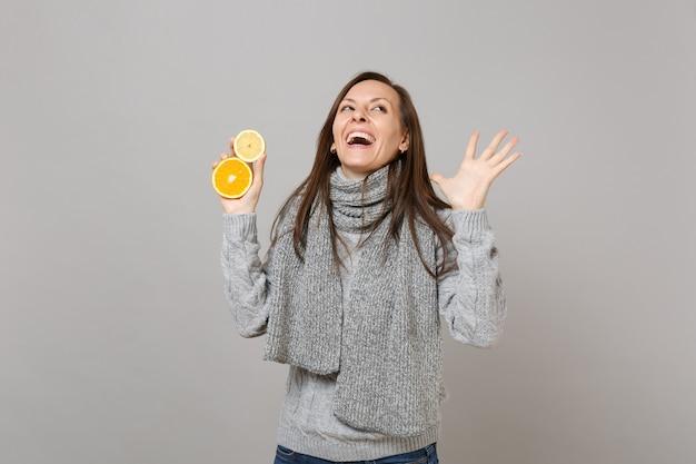 Ridendo giovane donna in maglione grigio, sciarpa guardando in alto, allargando le mani, tenendo limone, arancia isolato su sfondo grigio muro. stile di vita sano persone emozioni sincere concetto stagione fredda.