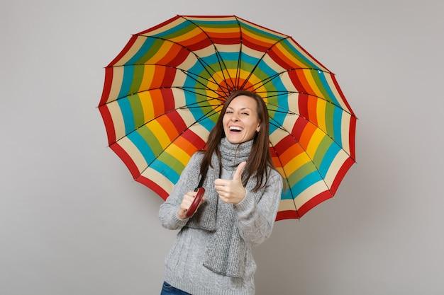 Ridendo giovane donna in maglione grigio, sciarpa che mostra il pollice in alto, tenendo ombrello colorato isolato su sfondo grigio. emozioni della gente di stile di vita sano di modo, concetto di stagione fredda. mock up copia spazio.