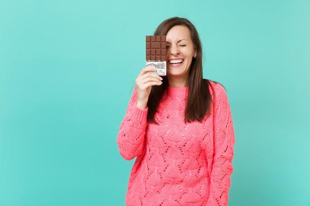 Ridendo giovane donna in maglia maglione rosa tenendo gli occhi chiusi, tenere in mano la barretta di cioccolato isolata su sfondo blu muro turchese, ritratto in studio. concetto di stile di vita della gente. mock up copia spazio.