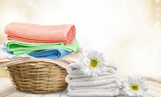 Cesto della biancheria con asciugamani colorati sullo sfondo